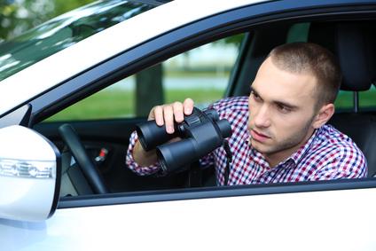 車から監視する男性