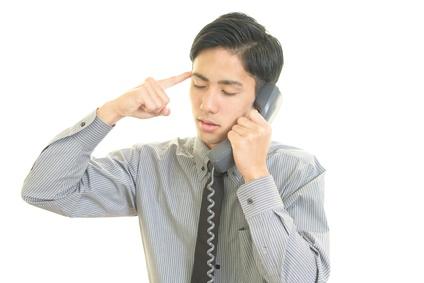 電話で苦悩するビジネスマン