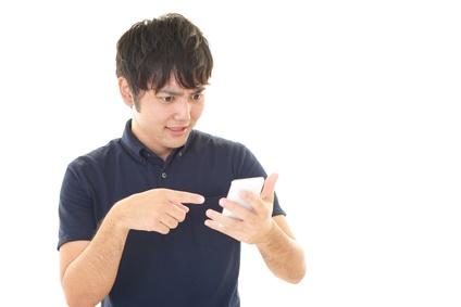 スマートフォンを見て驚く男性