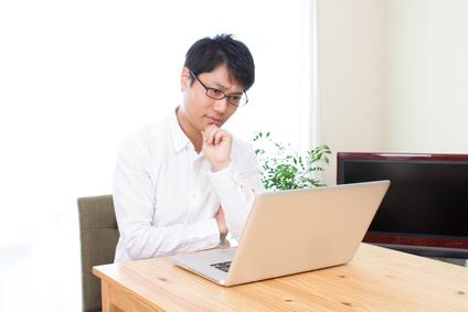 パソコンの前で悩む男性