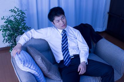 ソファーに腰をかける疲れたビジネスマン